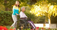 Senior woman in a wheelchair with caregiver